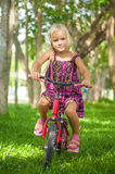 Adorable girl on bicycle in park on grass under trees Stock Image