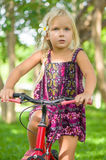 Adorable girl on bicycle in park on grass under trees Stock Photography