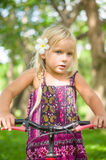 Adorable girl on bicycle in park on grass under trees Stock Images