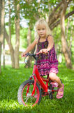 Adorable girl on bicycle in park on grass under trees Royalty Free Stock Images