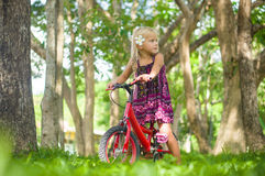 Adorable girl on bicycle in park on grass under trees Royalty Free Stock Photos