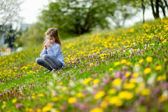 Adorable girl in blooming dandelion flowers Stock Photos