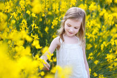 Adorable girl in blooming yellow flowers Stock Photos