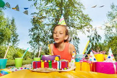 Adorable girl blowing candles on birthday cake royalty free stock photography