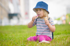 Adorable girl in blue hat eat ice cream on grass Stock Images