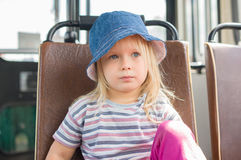 Adorable girl in blue hat ride on bus Stock Images
