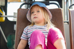 Adorable girl in blue hat ride on bus Royalty Free Stock Image