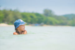 Adorable girl in blue hat swim in ocean near beach Stock Images