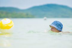 Adorable girl in blue hat swim in ocean near beach. Play with ye Royalty Free Stock Photo