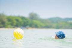Adorable girl in blue hat swim in ocean near beach. Play with ye Royalty Free Stock Images
