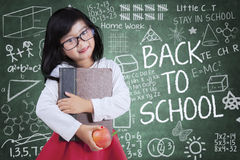 Adorable girl with book and apple in class Royalty Free Stock Photo