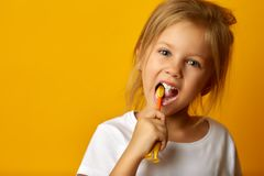 Adorable girl brushing teeth with kids toothbrush. Charming little girl in white t-shirt cleaning teeth with colorful kids toothbrush looking at camera royalty free stock images