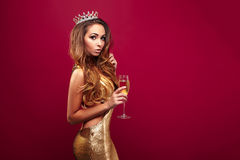 Adorable girl with champagne wearing crown royalty free stock photo