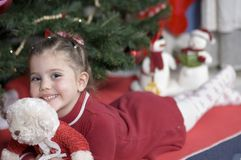 Adorable girl at Christmas time. In front of a Christmas tree a girl lies on her belly holding her teddy bear -Christmas snowmen in the background Stock Photography