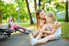 Adorable girl comforting her little sister after she fell off her bike at summer park. Child getting hurt while riding a bicycle. Active family leisure with stock photo