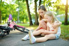 Adorable girl comforting her little sister after she fell off her bike at summer park. Child getting hurt while riding a bicycle. royalty free stock images
