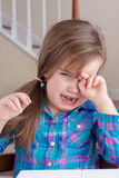 Adorable girl crying and wiping her eye Stock Photo
