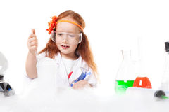 Adorable girl doing experiment, isolated on white Stock Photography