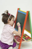 Adorable girl drawing on black board with chalk. Isolated on white background Stock Photography