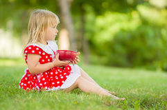 Adorable girl in dress with plate sit in park Stock Image