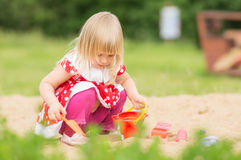 Adorable girl in dress play on sandbox Royalty Free Stock Images