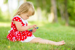 Adorable girl in dress play with smartphone Royalty Free Stock Photos