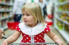 Adorable girl in dress ride on shopping cart Stock Photos