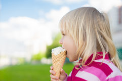 Adorable girl eat ice cream on green grass Stock Photography
