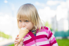 Adorable girl eat ice cream on green grass Royalty Free Stock Photo