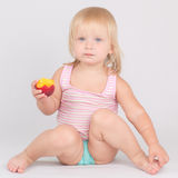 Adorable girl eat red fresh peach sitting on white Royalty Free Stock Photography