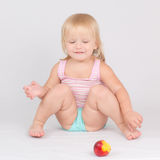 Adorable girl eat red fresh peach sitting on white Stock Photo