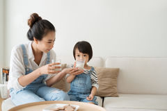 Adorable girl eating cookies and drinking milk with her mother. stock photography