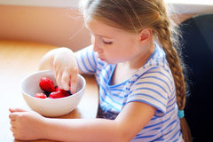 Adorable girl eating fresh berries. At kitchen Stock Images