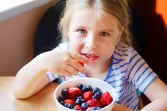 Adorable girl eating fresh strawberry. At kitchen Stock Photos