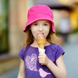 Adorable girl eating ice-cream outdoors at summer Royalty Free Stock Images