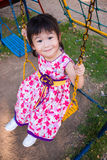 Adorable girl fun on swing in the park. Sunlight in the kids pla. Little asian child, adorable girl in pretty dress having fun on a swing and looking at the Royalty Free Stock Images