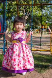 Adorable girl fun on swing in the park. Sunlight in the kids pla. Little asian child, adorable girl in pretty dress having fun on a swing in the park on summer Royalty Free Stock Photo