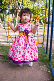 Adorable girl fun on swing in the park. Sunlight in the kids pla. Little asian child, adorable girl in pretty dress having fun on a swing in the park on summer Royalty Free Stock Photography