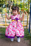 Adorable girl fun on swing in the park. Sunlight in the kids pla. Little asian child, adorable girl in pretty dress having fun on a swing in the park on summer Royalty Free Stock Image