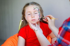 Adorable girl getting her face flower painted Royalty Free Stock Images