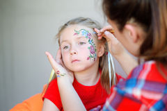 Adorable girl getting her face flower painted Stock Image
