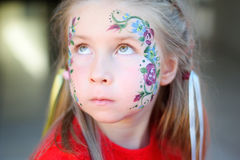 Adorable girl getting her face flower painted Royalty Free Stock Image