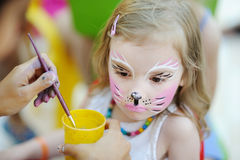 Adorable girl getting her face painted Royalty Free Stock Image