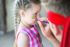 Adorable girl getting her face painted. At birthay party Stock Photo