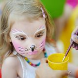 Adorable girl getting her face painted Stock Photo