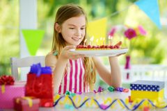Adorable girl having birthday party at home, blowing candles on birthday cake Stock Image