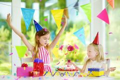 Adorable girl having birthday party at home, blowing candles on birthday cake Stock Photos