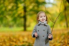 Adorable girl having fun on autumn day Stock Image