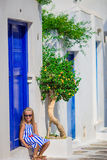 Adorable girl having fun outdoors. Kid at street of typical greek traditional village with blue door on greek island Stock Photo
