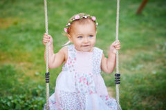 Adorable girl having fun on a swing on summer day Royalty Free Stock Image